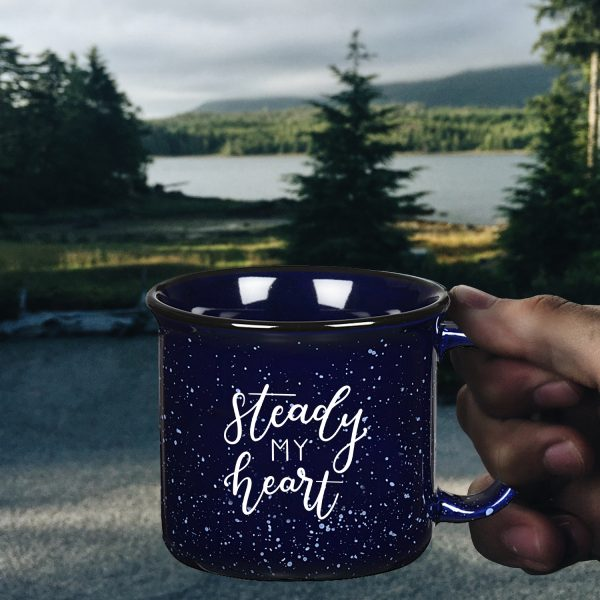 man holding steady my heart cobalt blue campfire mug with nature scene behind